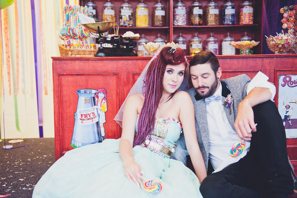 Bride and Groom sitting in front of sweet shop - photography by Laura Power - www.laurapower.co.uk